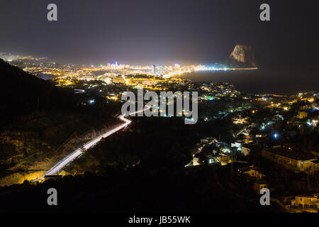 Highway road to the city, dark scenery, cityscape long exposure showing light trails - Stock Photo