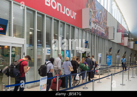 Montreal, CANADA - 8 June 2017: Travelers waiting in line to board bus in Montreal Coach terminal - Stock Photo