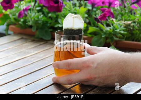 Menschliche Hand die ein Glas mit Teebeutel haelt. - Stock Photo
