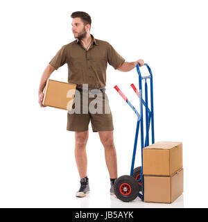 Male courier is standing close to push cart, holding package under his arm and looking away. Full length studio - Stock Photo