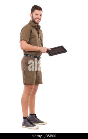 Smiling delivery man in khaki uniform is standing, holding digital tablet and pointing on it. Full length studio - Stock Photo