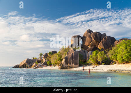Beautifully shaped granite boulders in illuminated by summer sun on picture perfect tropical Anse Source d'Argent - Stock Photo