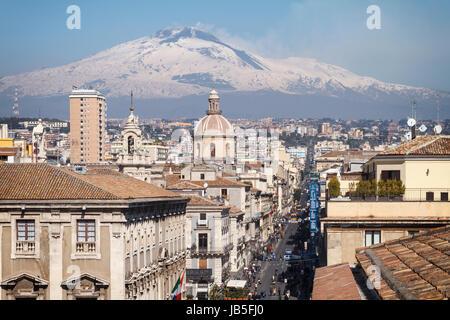 Catania, the central 'Via Etnea' street with the snow covered Mount Etna volcano, Sicily, Italy. - Stock Photo