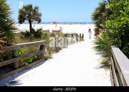 SIESTA KEY, FLORIDA - MAY 9, 2013: People entering very wide and colorful Siesta Beach on Siesta Key through a sand - Stock Photo
