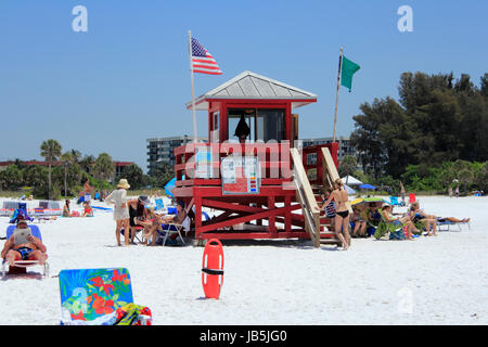 SIESTA KEY, FLORIDA - MAY 9, 2013: Red lifeguard tower flying green and American flags with a lifeguard present - Stock Photo