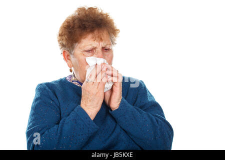 Picture of an elderly woman blowing her nose - Stock Photo