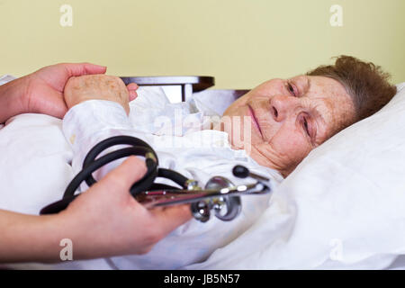 Picture of an elderly woman having a serious influenza - Stock Photo