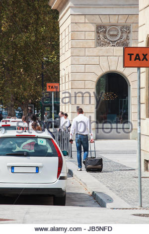 MILAN, ITALY - SEPTEMBER 20: Man with trolley waiting for taxi in Milan on September 20, 2013 - Stock Photo