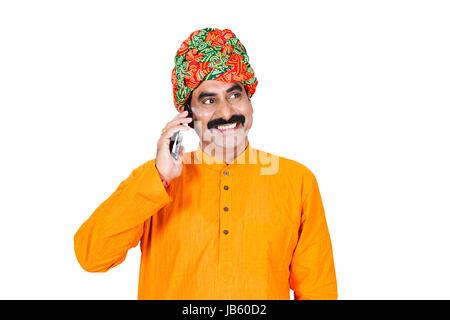 1 Indian Rural Rajasthani Man Talking On Mobile Phone Smiling On White Background - Stock Photo