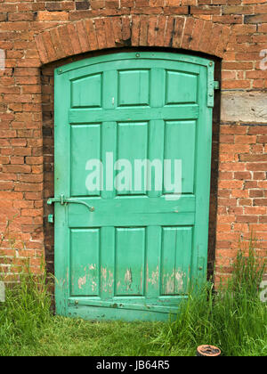 Old, green painted, panelled wooden door in red brick garden wall. - Stock Photo
