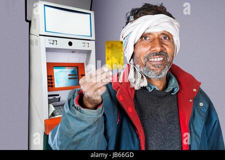 1 indian man atm machinery credit card showing stock photo 1 indian rural man using atm machine and showing credit card cash machine withdraw reheart Choice Image