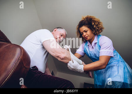 Caregiving Nurse putting a bandage on a senior mans arm in his home. - Stock Photo