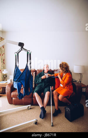 Homecare nurse checking a senior man with a stethoscope in his home. There is a hoist set up. - Stock Photo