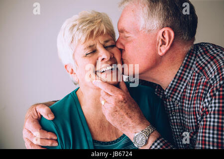 Senior man kissing his wife on the cheek. She has her eyes clsoed and is laughing. - Stock Photo