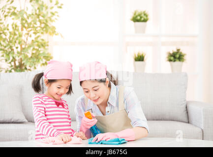 Happy family cleans the living room. Mother and daughter do the cleaning in the house. A young woman and a little - Stock Photo