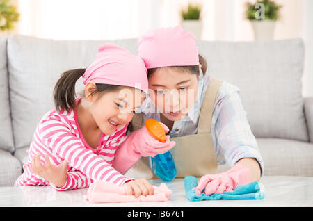 mixed race Asian Chinese mother and daughter do the cleaning in the house. Happy family cleans the room. A young - Stock Photo