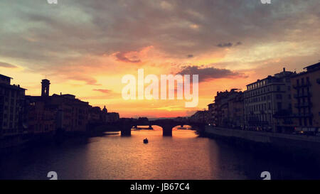 Sunset on the riviera over the bridge with the water reflecting the sky in Florence, Italy - Stock Photo
