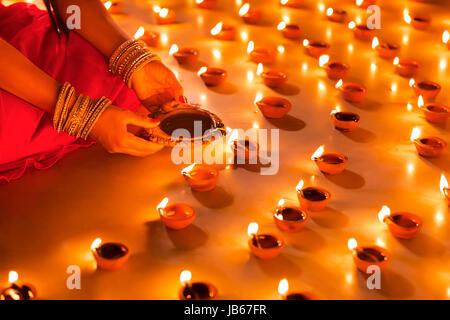 Traditional Indian woman lighting Diya Divali Festival - Stock Photo