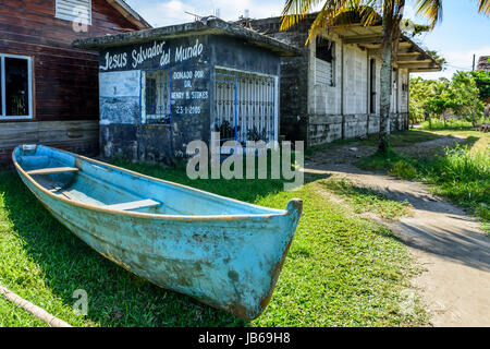 Livingston, Guatemala - August 31, 2016: Boat on grass outside beachside building in Caribbean town of Livingston, - Stock Photo