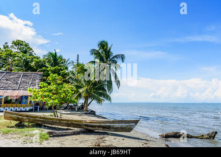 Livingston, Guatemala - August 31, 2016: Boat pulled ashore on beach in Caribbean town of Livingston - Stock Photo