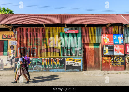 Livingston, Guatemala - August 31, 2016: Girls walk past colorfully painted walls in street in Caribbean town of - Stock Photo