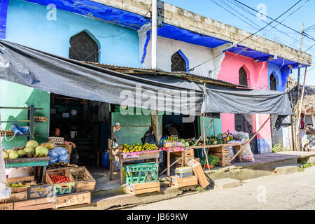 Livingston, Guatemala - August 31, 2016: Shopkeeper sits in doorway of grocery store in Caribbean town of Livingston - Stock Photo