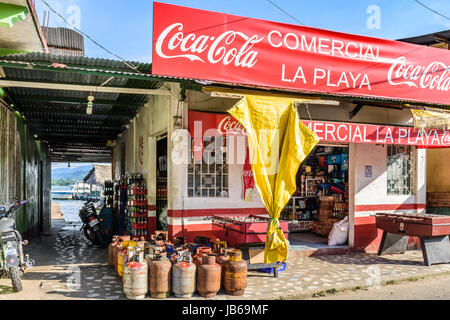 Livingston, Guatemala - August 31, 2016: Alleyway leads to moored boats at wooden dock next to riverside store in - Stock Photo