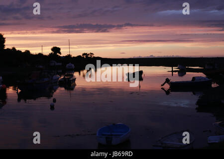 Beautiful sunset over harbour in Porlock Weir in Somerset, with black silhouettes of boats in water - Stock Photo