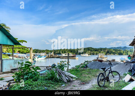 Livingston, Guatemala - August 31, 2016: Anchored fishing boats & workers in commercial dock area in Caribbean town - Stock Photo
