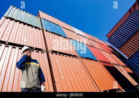 MODEL RELEASED. Man on cell phone with shipping containers. - Stock Photo