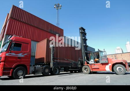 Forklift truck lifting shipping container. - Stock Photo