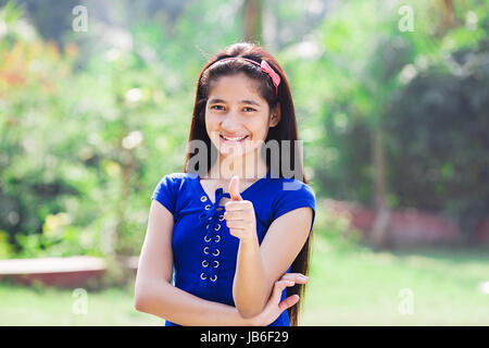 1 indian Teeanger Girl Standing In Park And Showing Thumbs up - Stock Photo