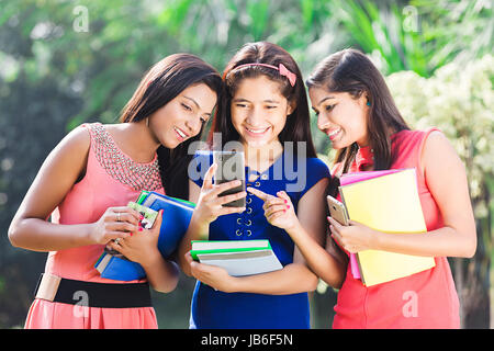 3 Indian College Teeanger Girls Standing In Park Messaging Phone - Stock Photo