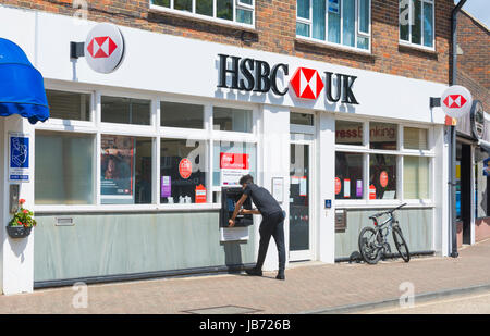 HSBC bank in the UK with person using cashpoint. - Stock Photo