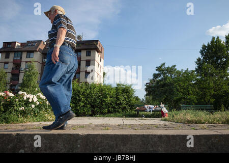 BELGRADE, SERBIA - JUNE 03, 2017: Old man walking near an senior woman sleeping on a bench, in the district of Doni - Stock Photo