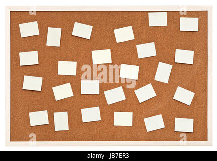 many small sheets of paper on bulletin cork board isolated on white background stock photo