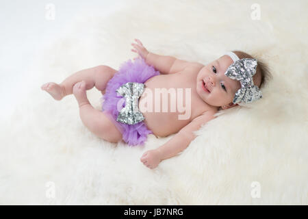 Portrait of a four month old baby girl wearing frilly, purple bloomers and a silver, sequin, bow headband. Shot - Stock Photo