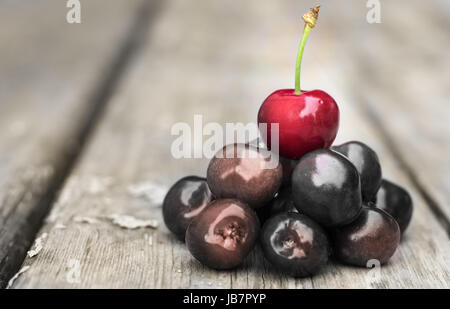 Conceptual image with cherries on a table, unique, individuality, different. - Stock Photo