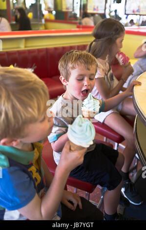 dh BOY CHILDREN children eating icecream cone boy licking ice cream Scarborough cafe - Stock Photo