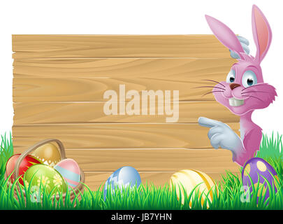 A cartoon pink Easter bunny rabbit peeping round a sign in green spring field full of chocolate decorated eggs - Stock Photo