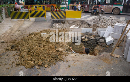 Man digging hole in road with spade, Kunming, China - Stock Photo
