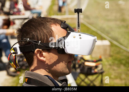 Drone pilot wearing first-person view headset. Young man driving a quadcopter using video-goggles - Stock Photo