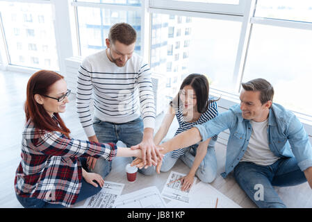 Joyful positive people holding their hands together - Stock Photo