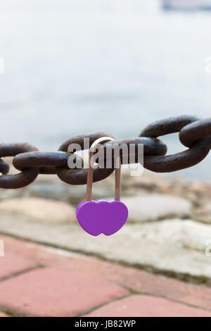 purple wedding lock hanging on the bridge - Stock Photo