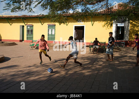 Young Cuban boys playing football in the streets of Trinidad Cuba - Stock Photo