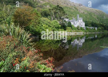 Kylemore abbey in beautiful nature and flowers in front - Stock Photo