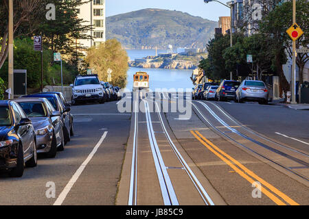 A cable car arriving at the top of a hill in San Francisco - Stock Photo