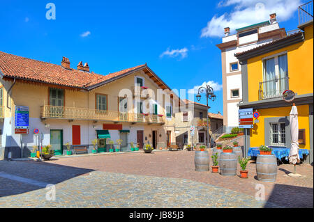 Small cobbled plaza at the center of typical italian town among colorful houses in Barolo, Italy. - Stock Photo