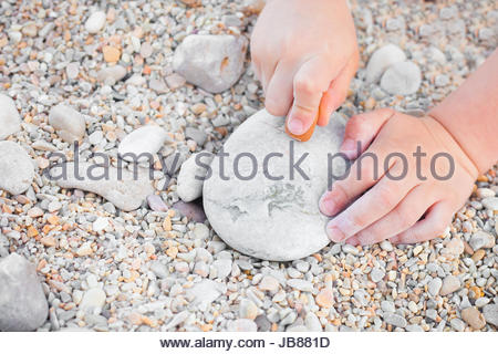 Close up of a young child's hands drawing on a stone - Stock Photo