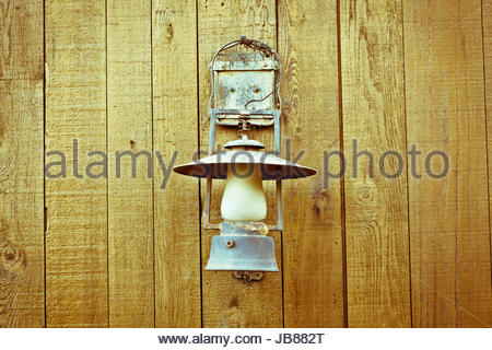 A nice vintage paraffin lamp mounted on a wooden wall - Stock Photo
